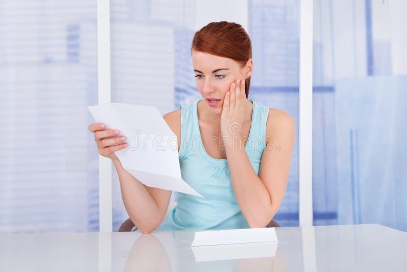 Συγκλονισμένη ανάγνωση Μπιλ γυναικών στο γραφείο στοκ εικόνα