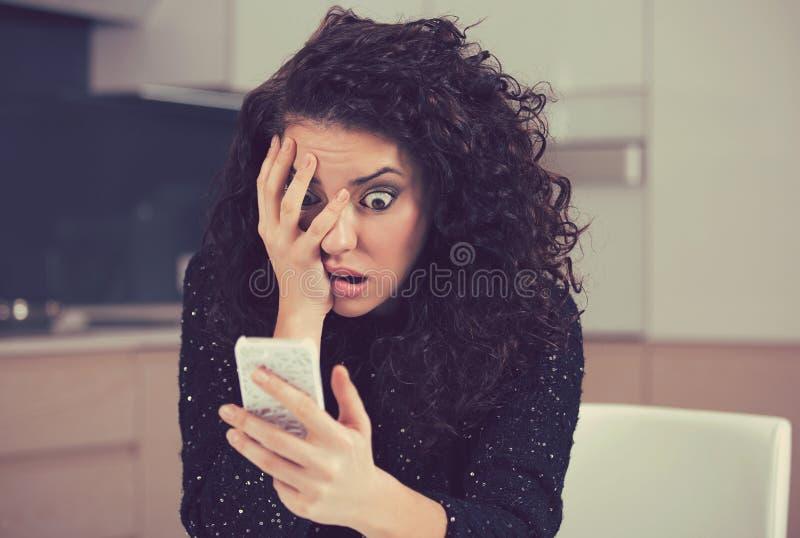 Συγκλονισμένη ανήσυχη γυναίκα που εξετάζει το τηλέφωνο που βλέπει το κακό μήνυμα ειδήσεων στοκ φωτογραφίες