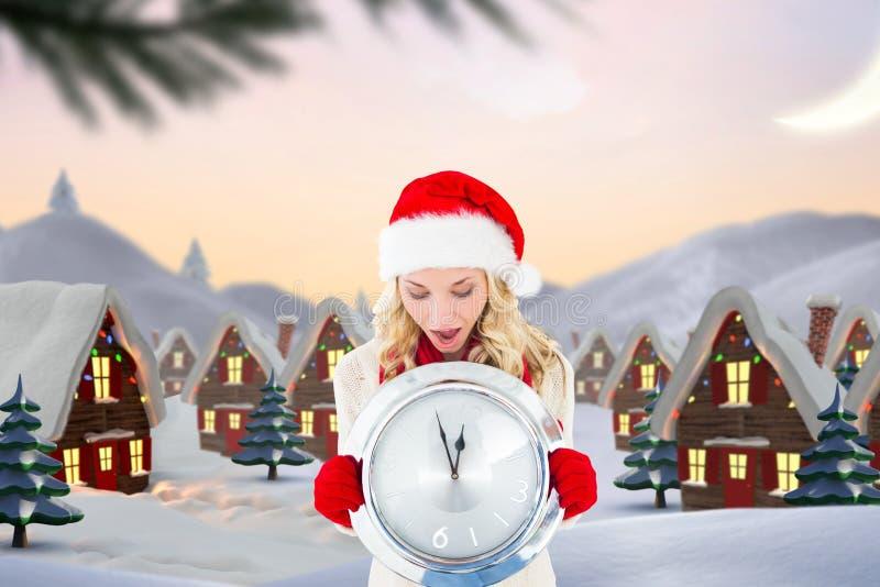 Συγκλονισμένη γυναίκα στο καπέλο santa που κρατά ένα ρολόι τοίχων απεικόνιση αποθεμάτων
