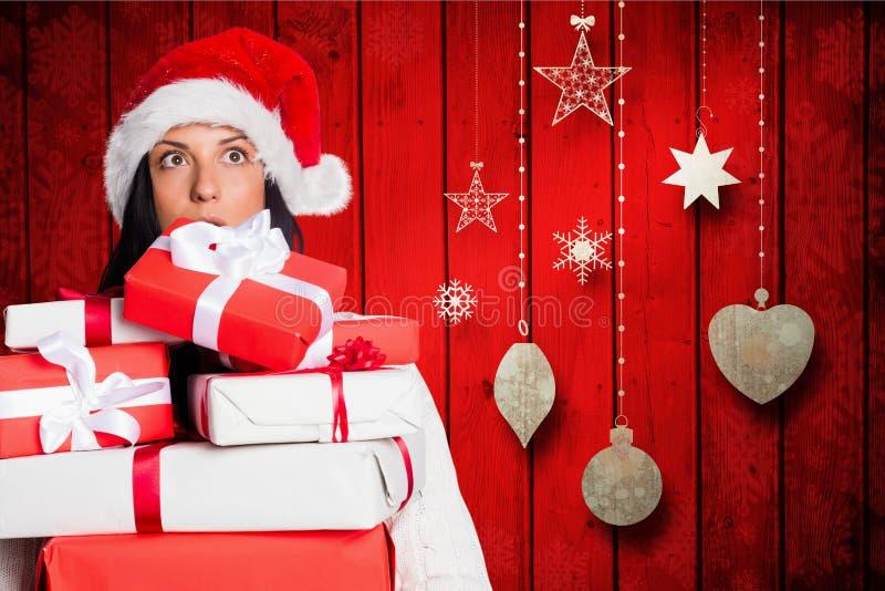 Συγκλονισμένη γυναίκα στο σωρό εκμετάλλευσης καπέλων santa των κιβωτίων δώρων στοκ εικόνες