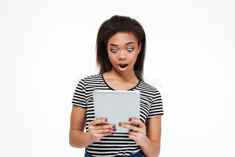 Συγκλονισμένη νέα αφρικανική γυναίκα που χρησιμοποιεί τον υπολογιστή ταμπλετών στοκ εικόνες με δικαίωμα ελεύθερης χρήσης