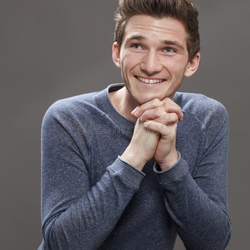 Συγκλονισμένος ευτυχής νέος άνδρας σπουδαστής με το κάθισμα χεριών στοκ εικόνες