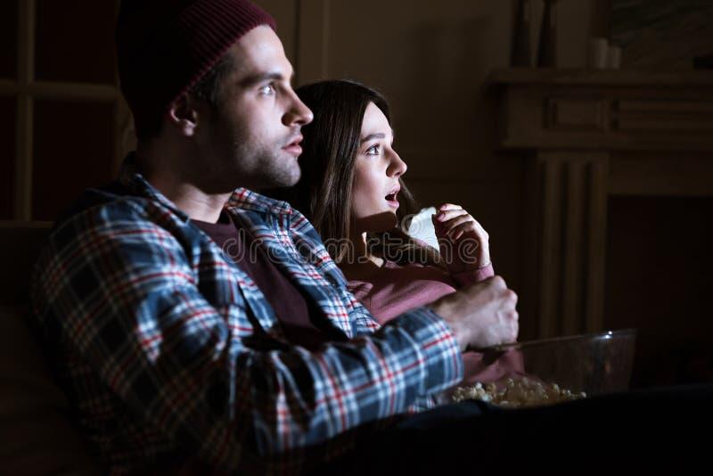 Συγκλονισμένος κινηματογράφος προσοχής ζευγών μαζί στο σπίτι στοκ φωτογραφία