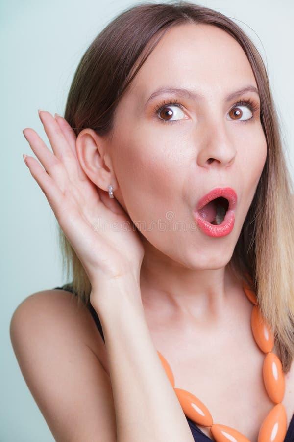 Συγκλονισμένο κορίτσι κουτσομπολιού που κρυφακούει με το χέρι στο αυτί στοκ φωτογραφία με δικαίωμα ελεύθερης χρήσης