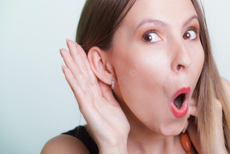 Συγκλονισμένο κορίτσι κουτσομπολιού που κρυφακούει με το χέρι στο αυτί στοκ εικόνα