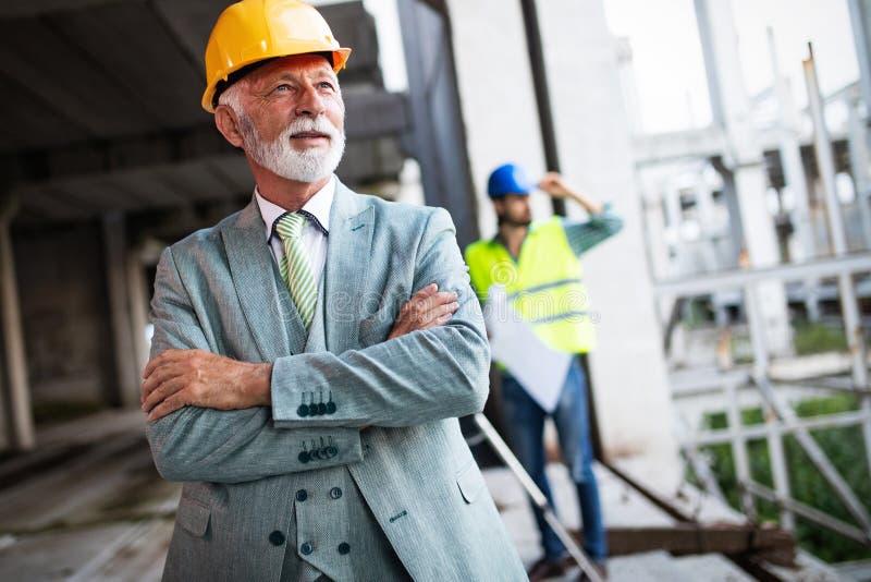 Συζήτηση μηχανικών κατασκευής με τους αρχιτέκτονες στην κατασκευή ή το εργοτάξιο στοκ εικόνα με δικαίωμα ελεύθερης χρήσης