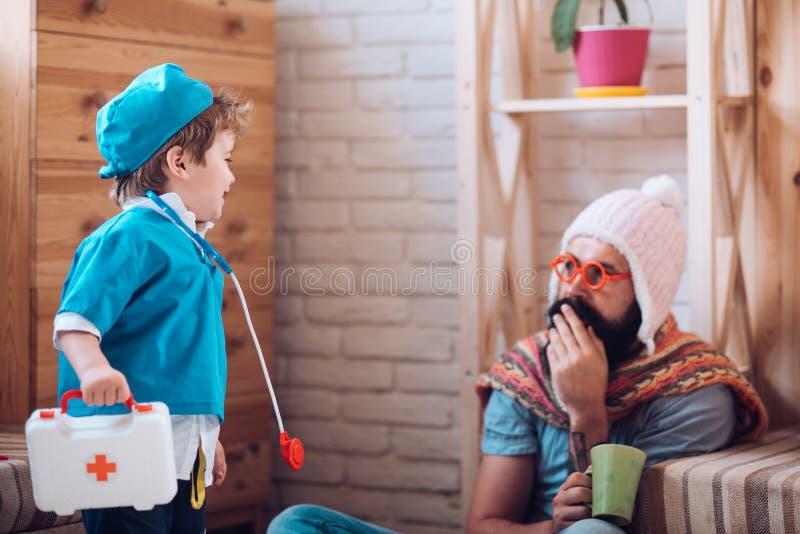 Συζήτηση της επεξεργασίας Ιατρική και υγεία Λίγος γιατρός παιδικού παιχνιδιού με το άτομο Ο γιος με το κιβώτιο πρώτων βοηθειών φρ στοκ φωτογραφίες με δικαίωμα ελεύθερης χρήσης