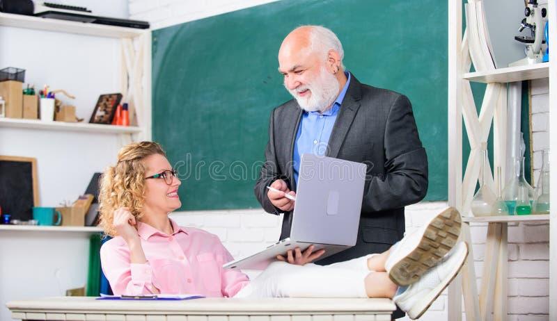Συζήτηση του θέματος με το σπουδαστή ή το συνάδελφο Ώριμος δάσκαλος σχολείου ατόμων και ξένοιαστος σπουδαστής κοριτσιών με το lap στοκ εικόνες