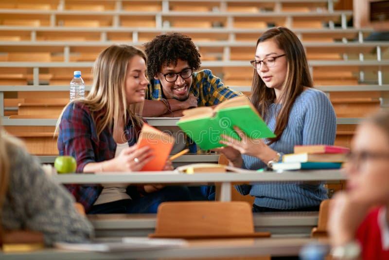 Συζήτηση του σπουδαστή χαμόγελου και γράψιμο μαζί στο κολλέγιο στοκ φωτογραφία με δικαίωμα ελεύθερης χρήσης
