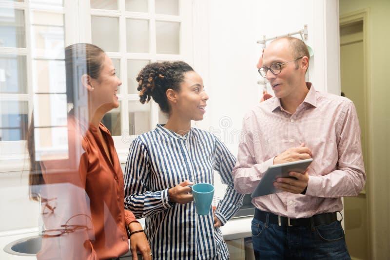 Συζήτηση τριών επιχειρησιακών συναδέλφων σε ένα γραφείο kitche στοκ εικόνα με δικαίωμα ελεύθερης χρήσης