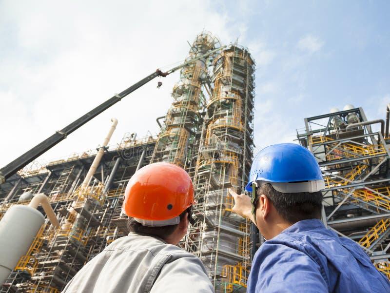 Συζήτηση δύο βιομηχανικών εργατών και υπόδειξη για μέσα στοκ φωτογραφία