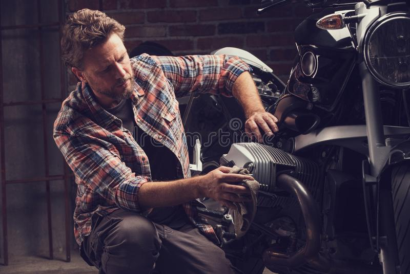 Συλλέκτης ή μηχανικός που εργάζεται σε μοτοσικλέτα στοκ φωτογραφίες