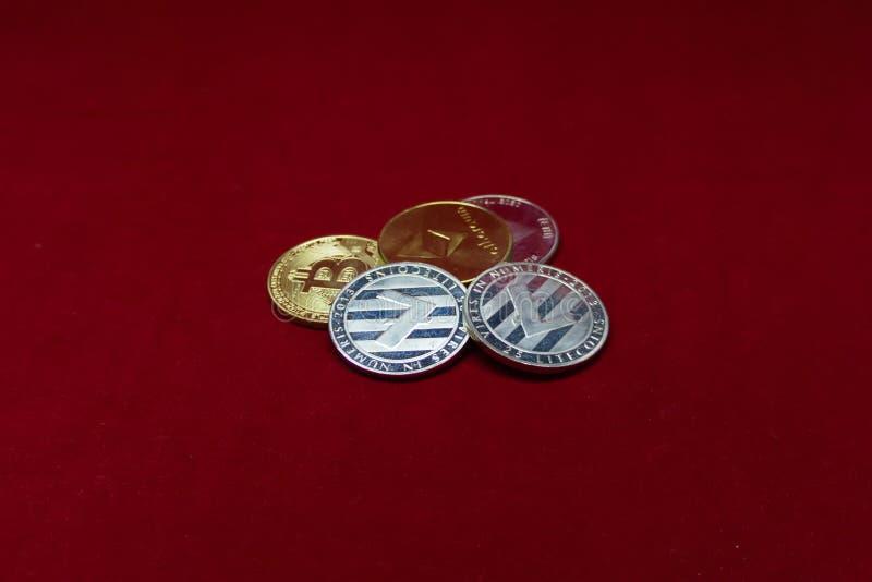 Συλλογή των νομισμάτων cryptocurrency με το litecoin στο μέτωπο και bitcoin και το ethereum στην πλάτη στο κόκκινο βελούδο ελεύθερη απεικόνιση δικαιώματος
