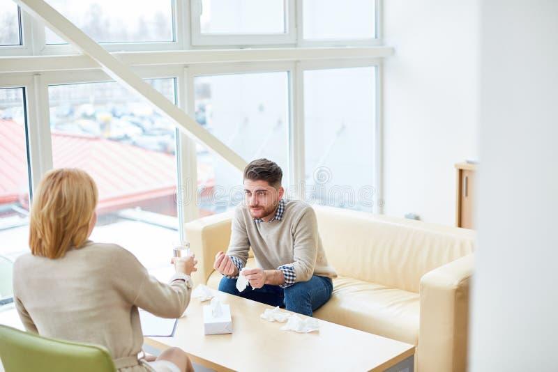 Συμβουλευτικός άνδρας γυναικών κατά τη διάρκεια της θεραπείας στοκ φωτογραφία