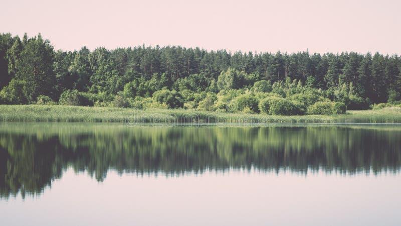 συμμετρικές αντανακλάσεις στην ήρεμη λίμνη - ο αναδρομικός τρύγος κοιτάζει στοκ εικόνα