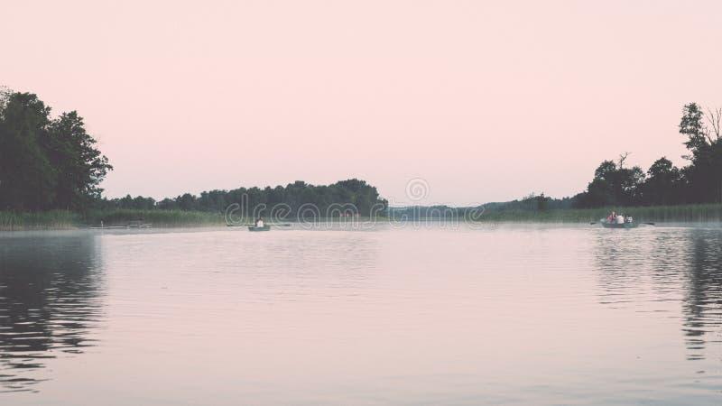 συμμετρικές αντανακλάσεις στην ήρεμη λίμνη - ο αναδρομικός τρύγος κοιτάζει στοκ εικόνες