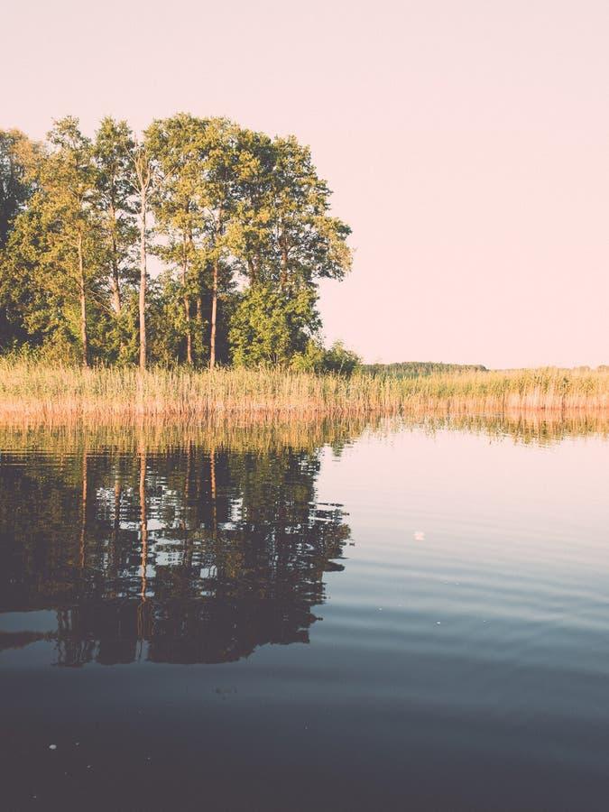συμμετρικές αντανακλάσεις στην ήρεμη λίμνη - ο αναδρομικός τρύγος κοιτάζει στοκ φωτογραφίες