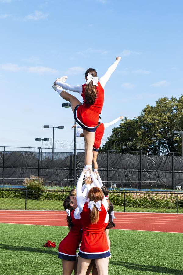 Συμπαίκτης εκμετάλλευσης γυμνασίου cheerleardess επάνω από τους αστραγάλους τους στοκ εικόνες