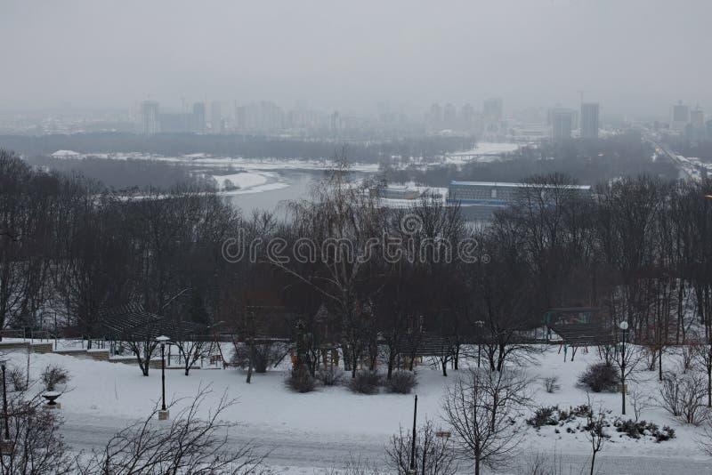 συμπαθητικός χειμώνας το Πρωί στην πόλη Παιδική χαρά παιδιών ` s στο πάρκο Τα κτήρια κρύβουν στην ομίχλη στην αριστερή τράπεζα στοκ εικόνες