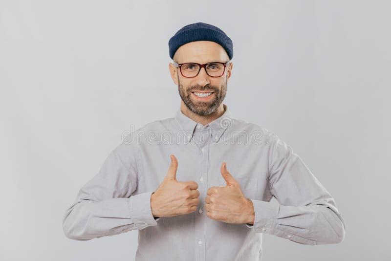 Συμπαθώ αυτήν την ιδέα! Το ευτυχές αξύριστο άτομο αυξάνει τους αντίχειρες επάνω, χαμογελά ευρέως, ικανοποιώντας με τη μεγάλη επιλ στοκ φωτογραφία με δικαίωμα ελεύθερης χρήσης