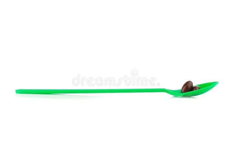 συμπληρωματικός Βιταμίνη Ε Κατανάλωση Πράσινο κουτάλι Απομονωμένος στο μόριο στοκ φωτογραφία με δικαίωμα ελεύθερης χρήσης