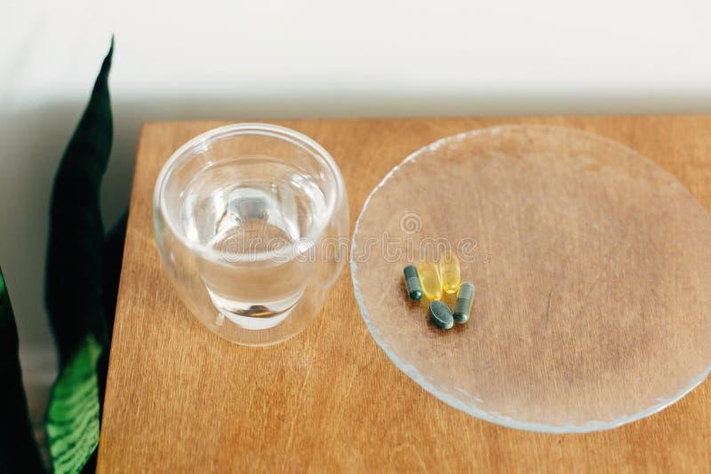 Συμπληρώματα διατροφής, βιολογικά δραστικά πρόσθετα Ωμέγα 3, σπιρουλίνα, καψάκια χλωροφύλλης και ποτήρι νερό σε ξύλινο τραπέζι στοκ φωτογραφίες