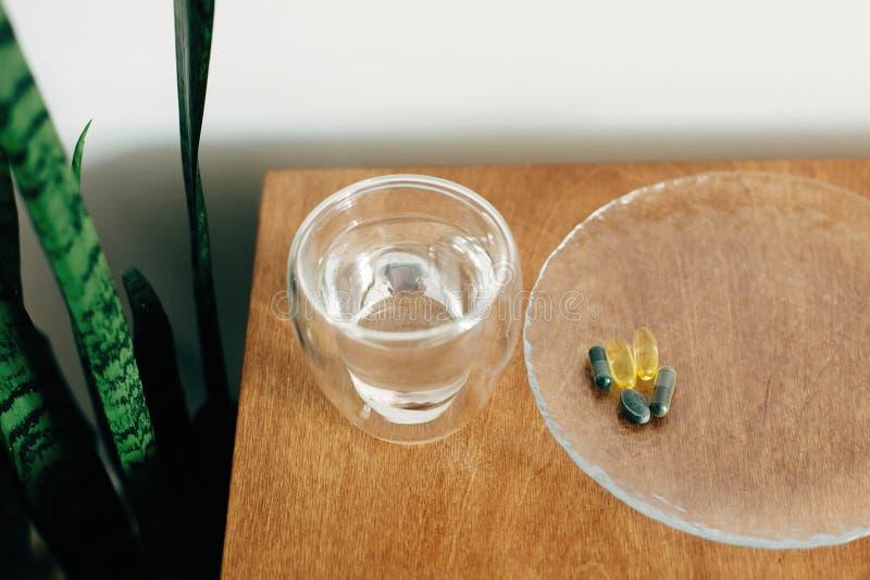 Συμπληρώματα διατροφής, βιολογικά δραστικά πρόσθετα Ωμέγα 3, σπιρουλίνα, καψάκια χλωροφύλλης και ποτήρι νερό σε ξύλινο τραπέζι στοκ εικόνες
