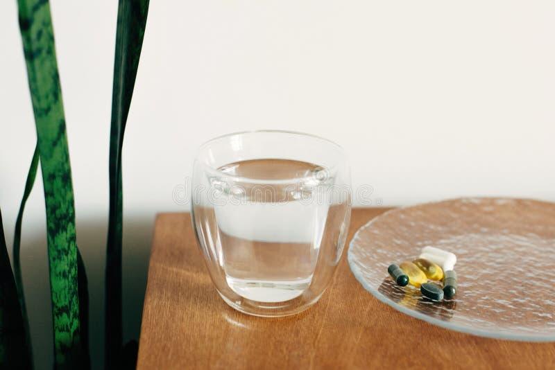Συμπληρώματα διατροφής, βιολογικά δραστικά πρόσθετα Omega 3, σπιρουλίνα, χλωροφύλλη, καψάκια μαγνησίου και γυαλί νερού σε ξύλινη  στοκ φωτογραφίες