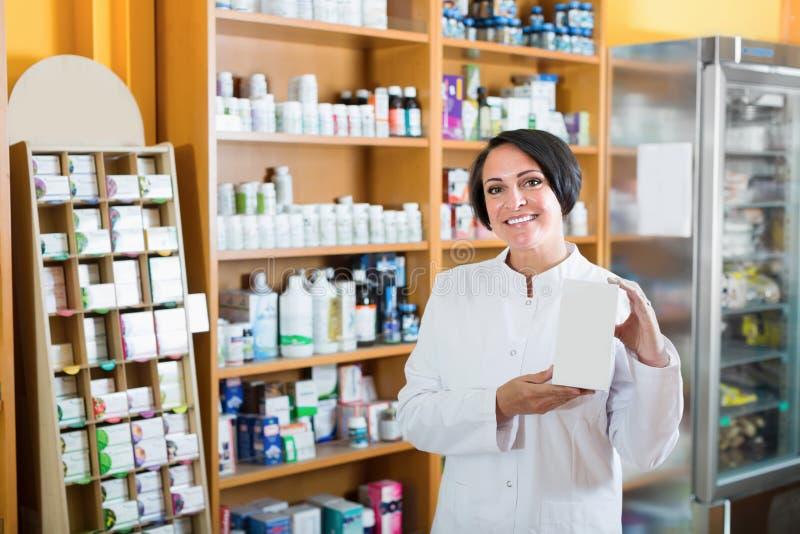 Συμπλήρωμα εκμετάλλευσης πωλητών χαμόγελου ώριμο θηλυκό στο κιβώτιο στοκ εικόνα με δικαίωμα ελεύθερης χρήσης
