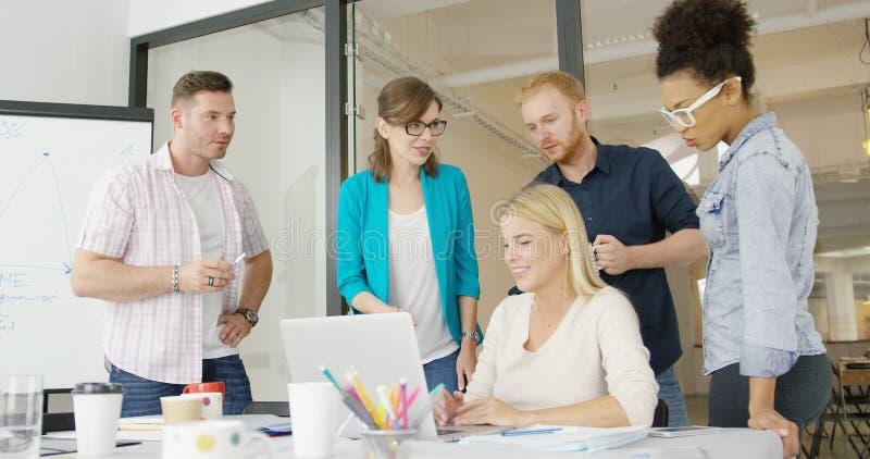 Συνάδελφοι με το lap-top στην αρχή στοκ φωτογραφίες