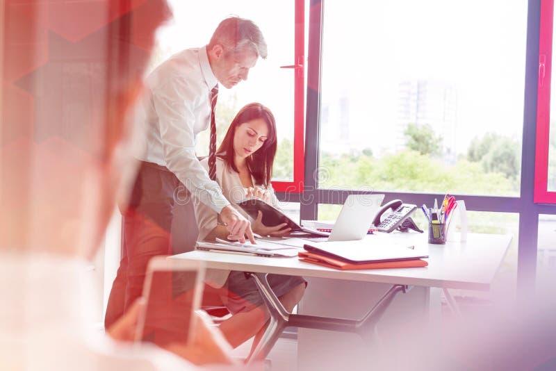 Συνάδελφοι πέρα από το έγγραφο στη συζήτηση στο γραφείο στην αρχή στοκ φωτογραφία