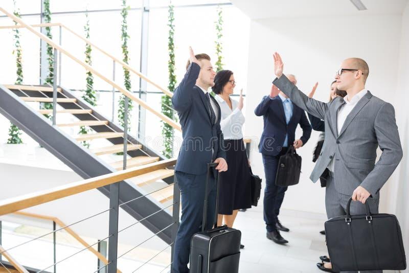Συνάδελφοι που δίνουν Highfive στεμένος στο σύγχρονο γραφείο στοκ φωτογραφία με δικαίωμα ελεύθερης χρήσης