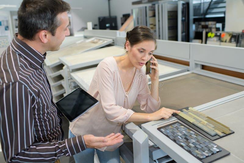 Συνάδελφοι που κρατούν την ψηφιακή ταμπλέτα και το κινητό τηλέφωνο στο δημιουργικό γραφείο στοκ εικόνες