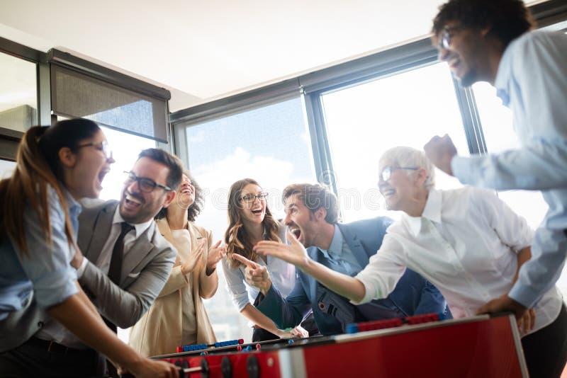 Συνάδελφοι που παίζουν το επιτραπέζιο ποδόσφαιρο στο σπάσιμο από την εργασία στοκ εικόνα