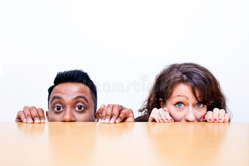 Συνάδελφοι εργασίας που κρυφοκοιτάζουν πέρα από την άκρη του πίνακα στοκ εικόνα