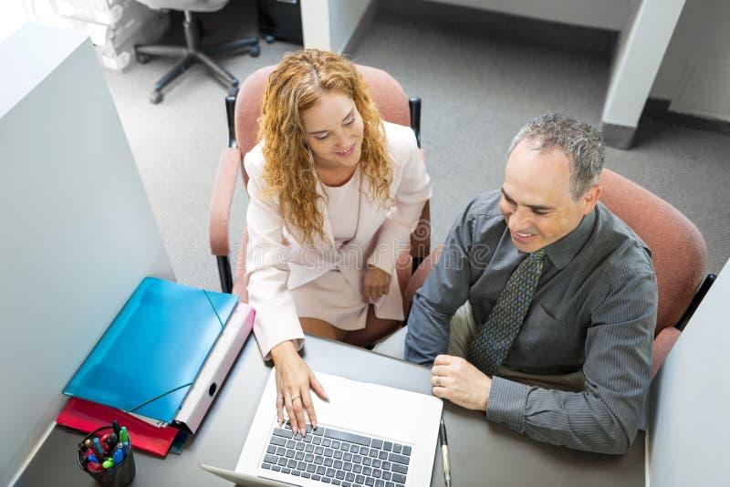 Συνάδελφοι που εξετάζουν τον υπολογιστή στην αρχή στοκ φωτογραφία με δικαίωμα ελεύθερης χρήσης