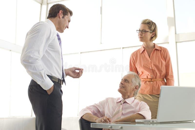 Συνάδελφοι που διοργανώνουν τη συζήτηση στην αίθουσα συνεδριάσεων στοκ εικόνες