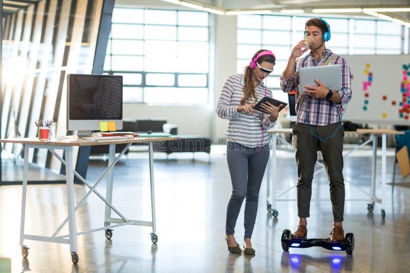 Συνάδελφοι που χρησιμοποιούν την ψηφιακά ταμπλέτα και το lap-top στοκ εικόνες