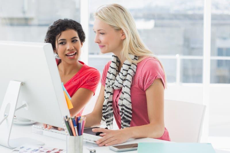 Συνάδελφοι που χρησιμοποιούν τον υπολογιστή στο φωτεινό γραφείο στοκ εικόνες