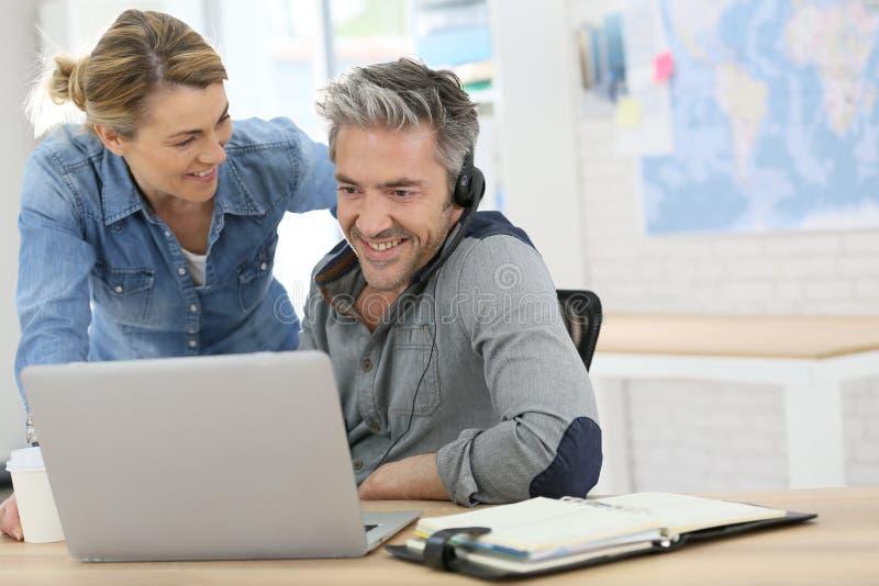 Συνάδελφοι στο γραφείο που λειτουργεί στο lap-top στοκ εικόνα