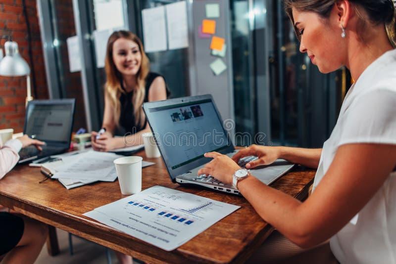 Συνέταιροι που έχουν μια συνεδρίαση συνεδρίασης στο γραφείο με τα lap-top στη αίθουσα συνδιαλέξεων στοκ φωτογραφίες