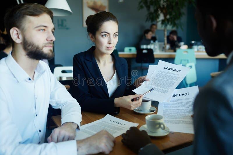 Συνέταιροι που συζητούν τη διαπραγμάτευση στον πίνακα συνεδρίασης στοκ εικόνες