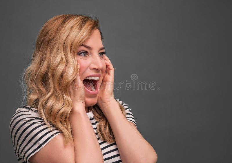 Συναισθηματικές ξανθές κραυγές Εκφοβισμένη τεντώνοντας στάση κραυγής γυναικών σε ένα γκρίζο υπόβαθρο στοκ φωτογραφία με δικαίωμα ελεύθερης χρήσης