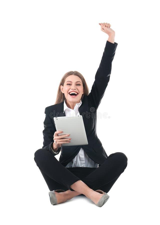 Συναισθηματική επιχειρηματίας στην ένδυση γραφείων με τη νίκη εορτασμού ταμπλετών στο λευκό στοκ εικόνες