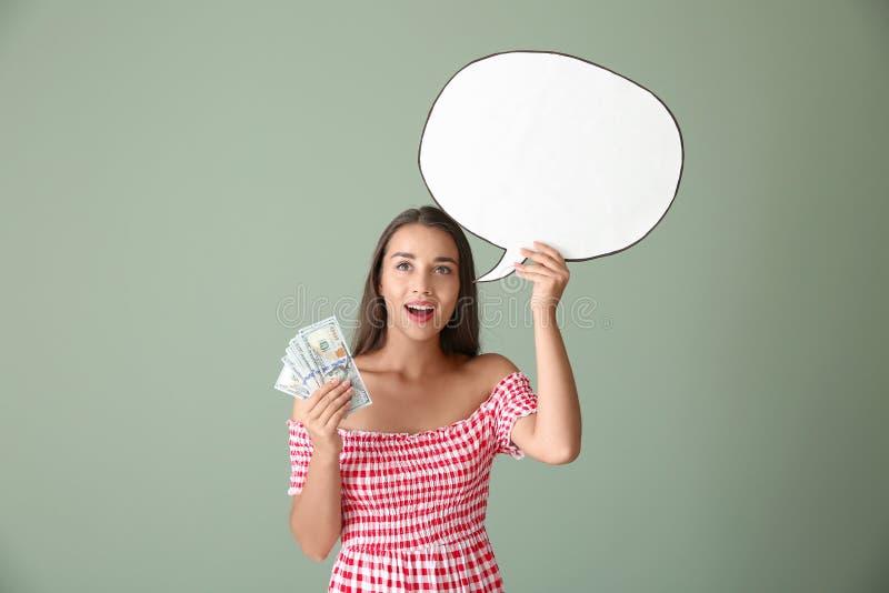 Συναισθηματική νέα γυναίκα με τα χρήματα και κενή λεκτική φυσαλίδα στο υπόβαθρο χρώματος στοκ φωτογραφία με δικαίωμα ελεύθερης χρήσης