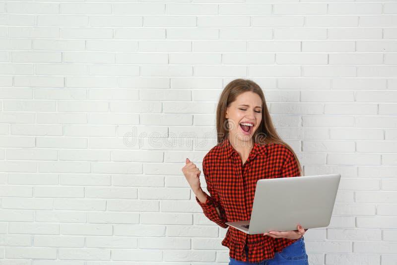Συναισθηματική νέα γυναίκα με τη νίκη εορτασμού lap-top κοντά στο τουβλότοιχο στοκ φωτογραφία με δικαίωμα ελεύθερης χρήσης
