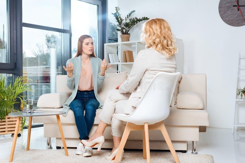 συναισθηματική νέα γυναίκα που μιλά με τον ψυχολόγο στοκ εικόνες