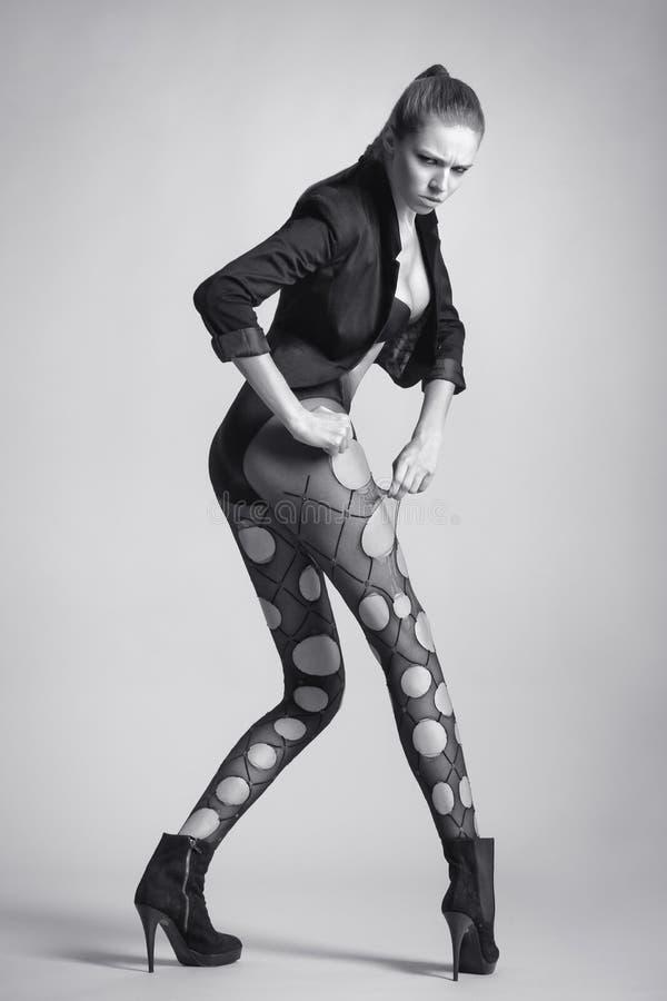 Συναισθηματική προκλητική γυναίκα με τα μακριά πόδια στις γυναικείες κάλτσες διαμορφώστε το κορίτσι στοκ φωτογραφία
