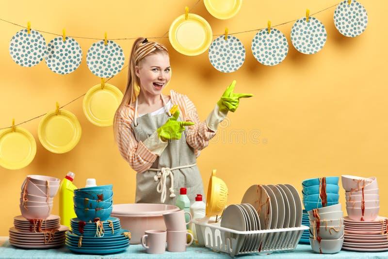 Συναισθηματική τρομερή ξανθομάλλης γυναίκα που παρουσιάζει καθαρά πιάτα της στα clothespins στοκ φωτογραφία με δικαίωμα ελεύθερης χρήσης