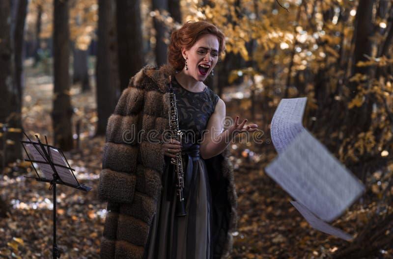 Συναισθηματικός γυναίκα-ομποΐστας που κρατά ένα όμποε που ρίχνει μακριά τα μουσικά φύλλα στοκ εικόνα με δικαίωμα ελεύθερης χρήσης